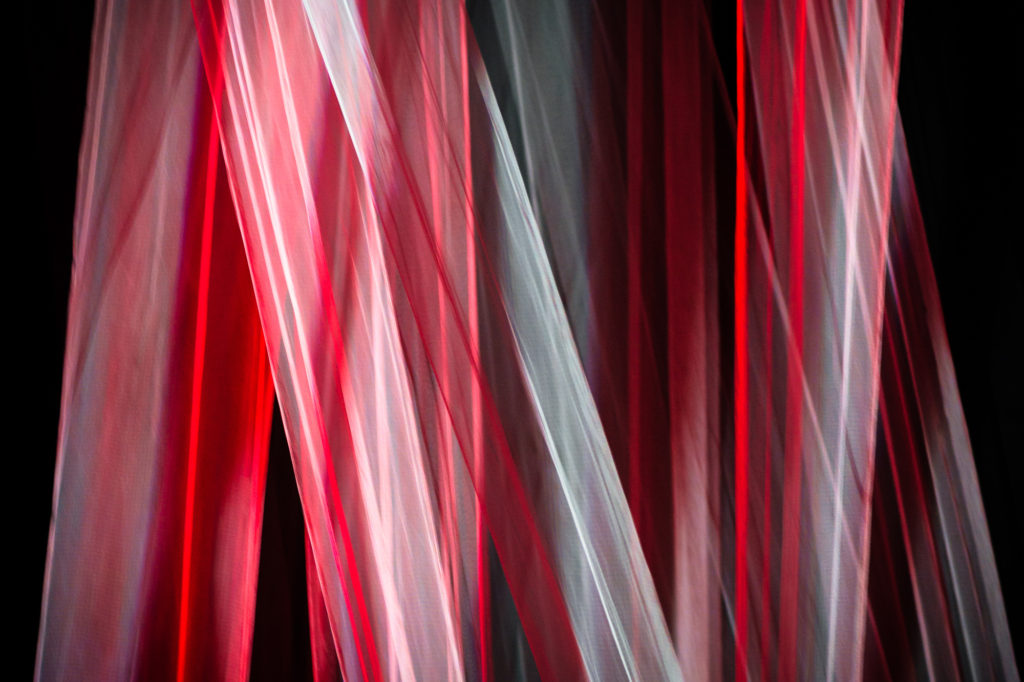 The hanging fabric backdrop lit red and white